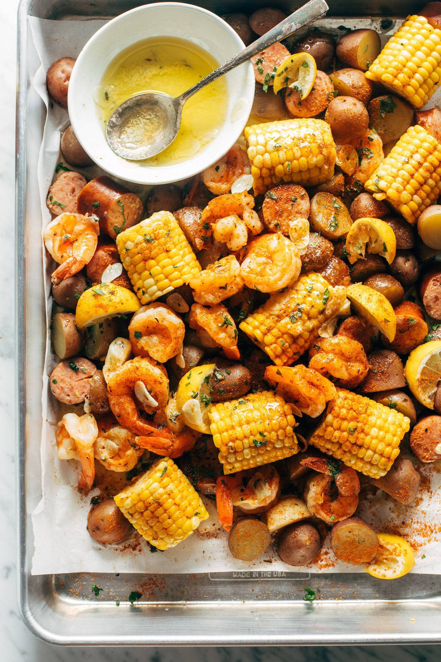 Shrimp boil on a sheet pan with garlic butter. The garlic butter is in a bowl with a spoon and there's corn, lemon wedges, shrimp, and kielbasa on the sheet pan with potatoes.