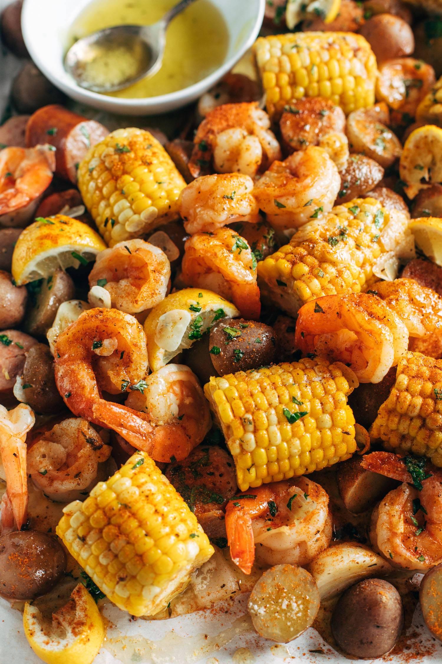 Corn, shrimp, onions, and kielbasa sausage on a platter for a shrimp boil.