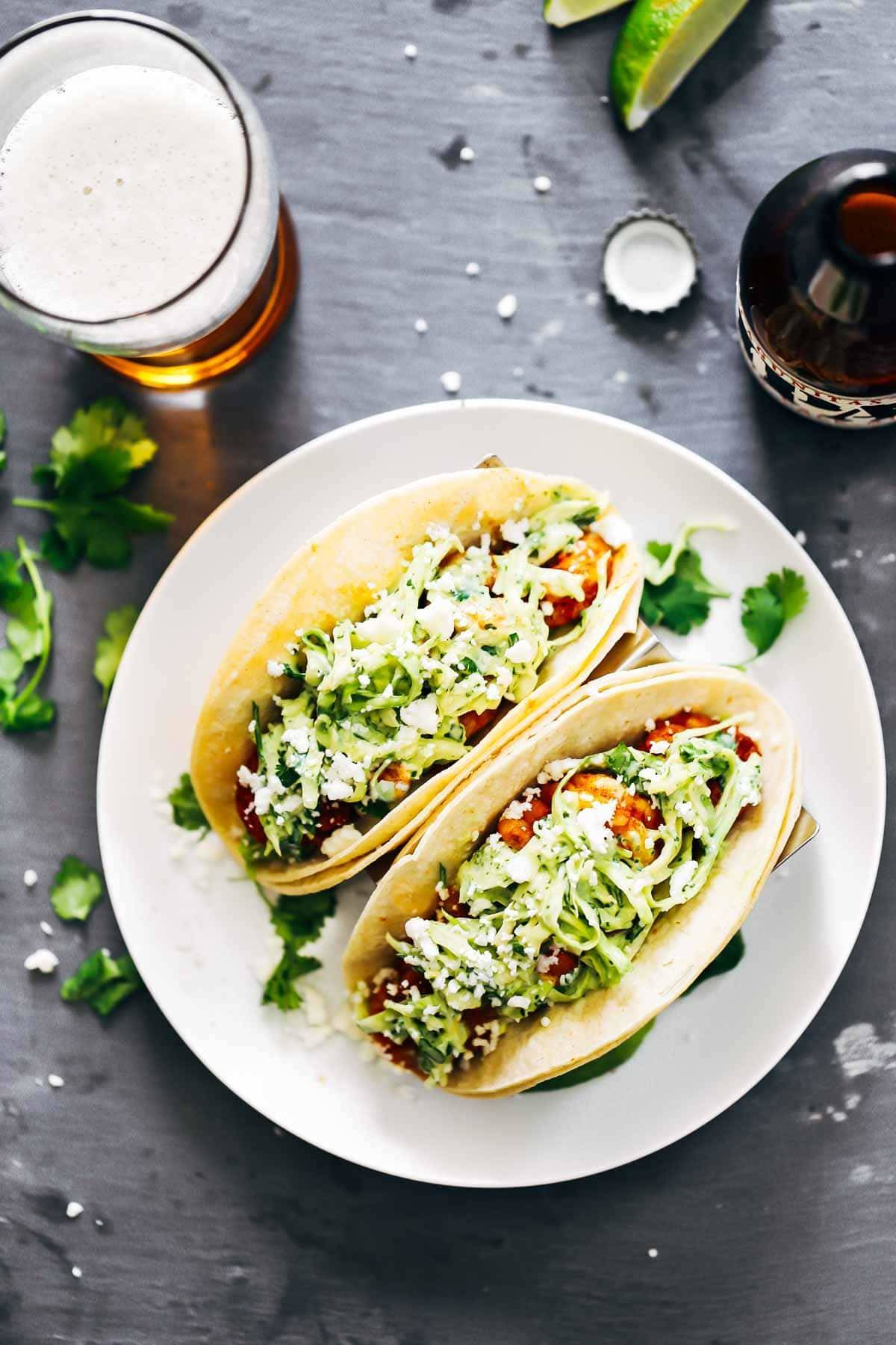 Spicy Shrimp Tacos in taco holders with a glass of beer.