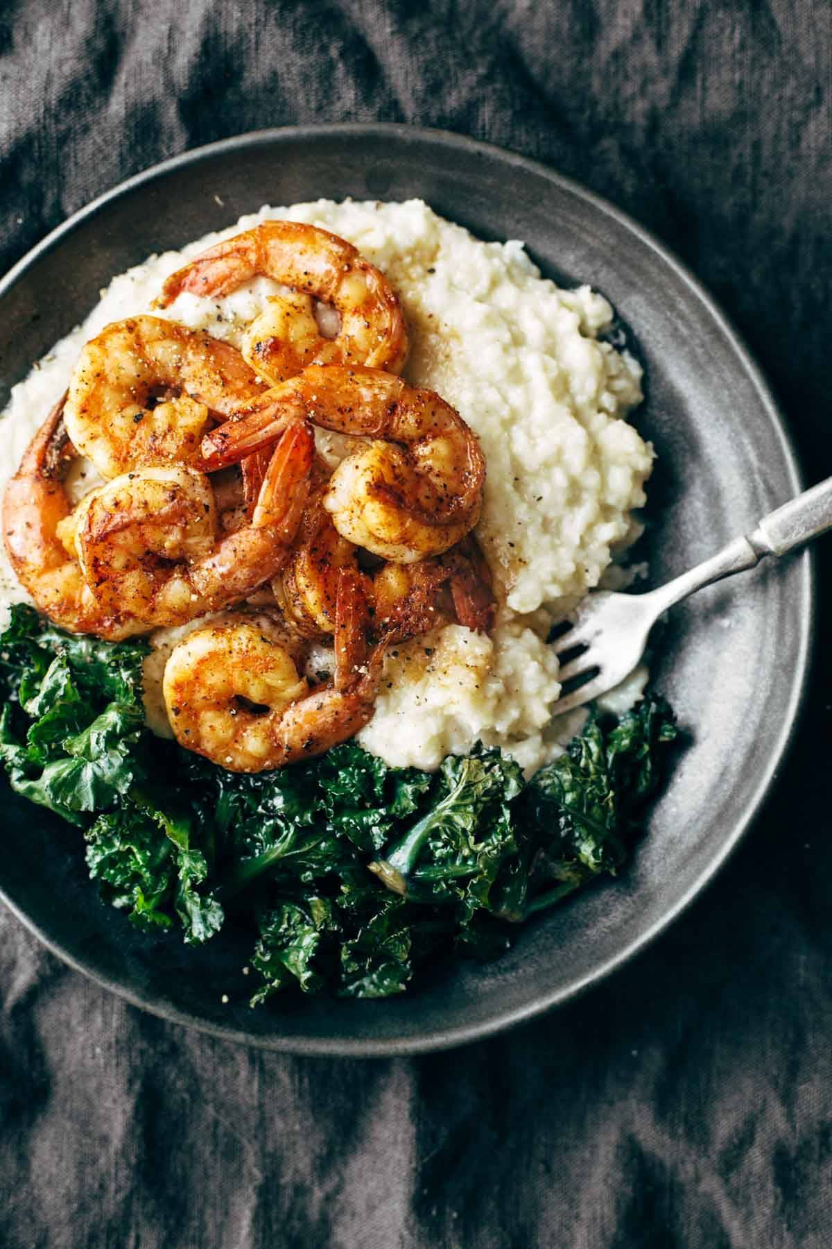 Shrimp with cauliflower mash and kale on a plate with a fork.