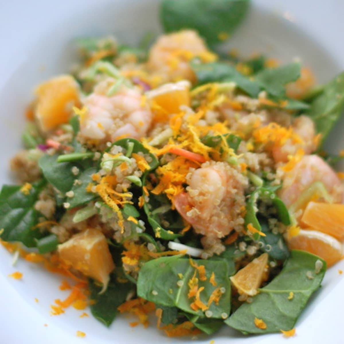 Shrimp and quinoa salad in a bowl with orange zest topping.