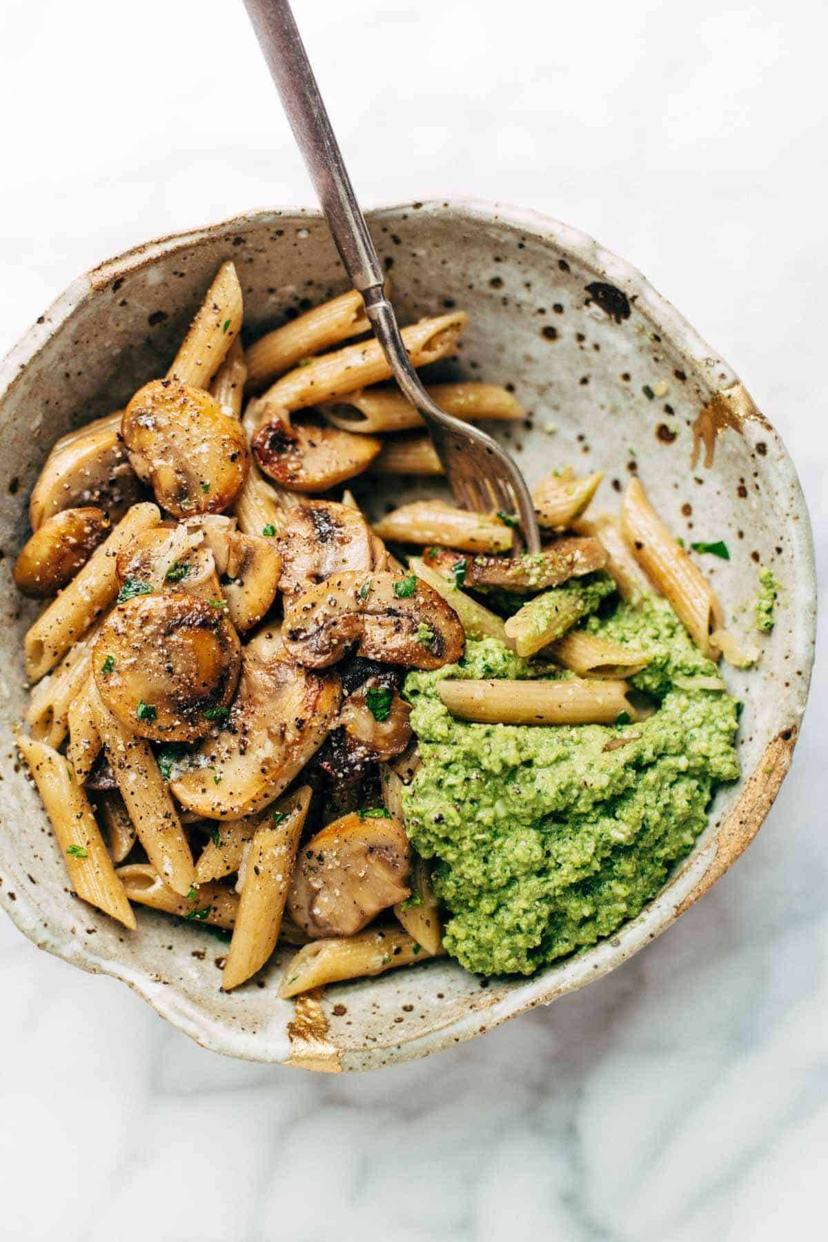 Simple Mushroom Penne with Walnut Pesto in a speckled bowl.