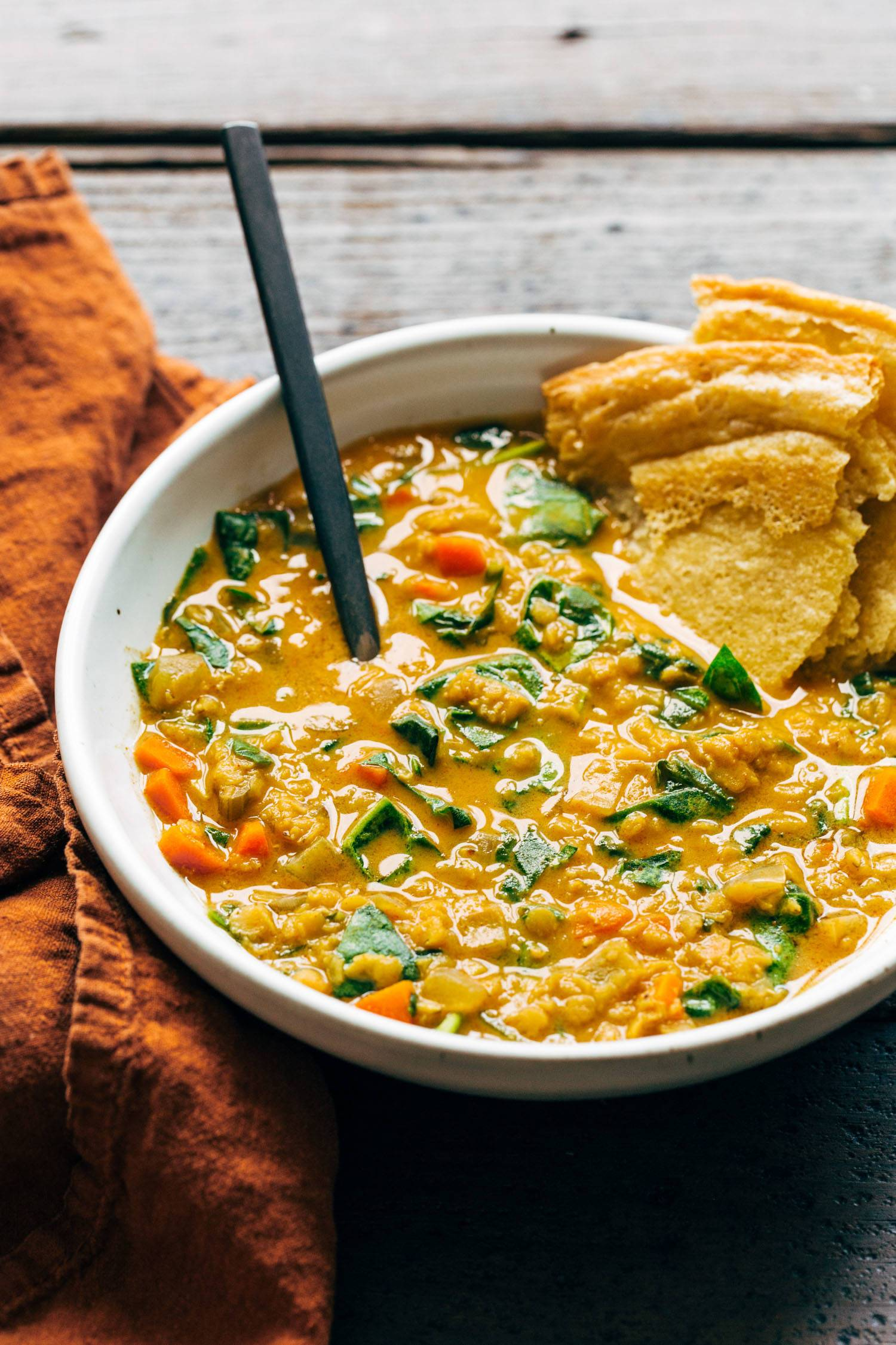 Red lentil soup with spinach and socca in a bowl with a spoon.