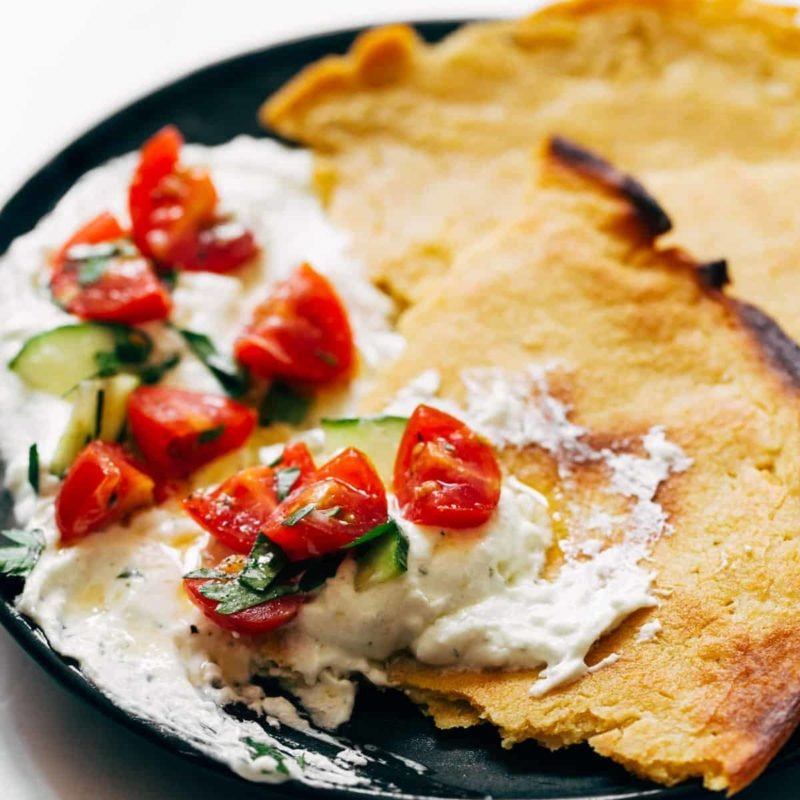 Socca with Whipped Feta and Tomato Salad on a plate.