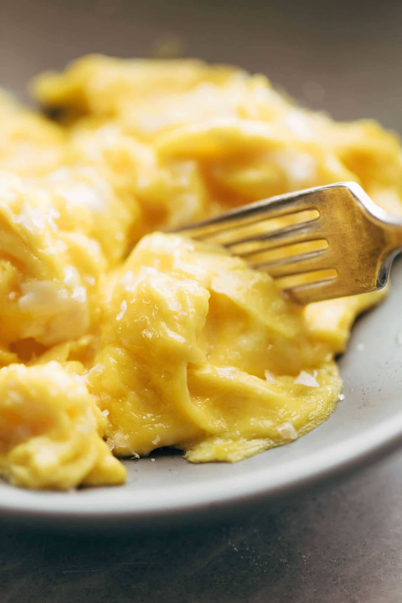 soft scrambled eggs with a fork on a plate