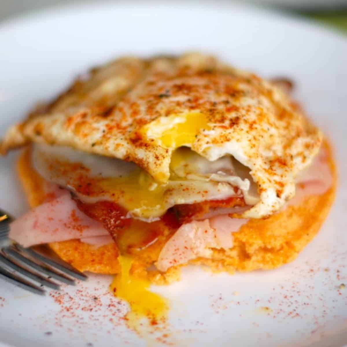 This spicy corn cake breakfast stack is a savory Mexican spin on pancakes - the little corn cakes topped with bacon and fried eggs is to die for! | pinchofyum.com