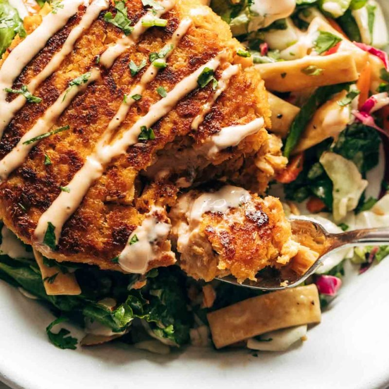 Salmon burgers on a bed of Mixed Greens in a bowl.