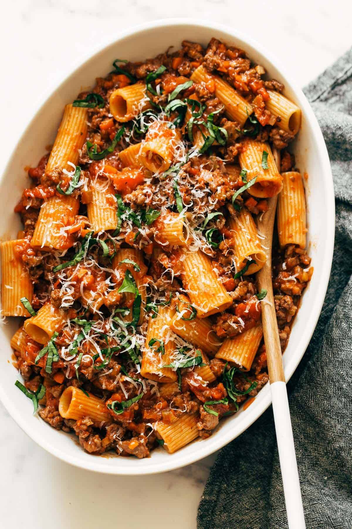 Spicy Sausage Rigatoni in a serving dish with wooden spoon.