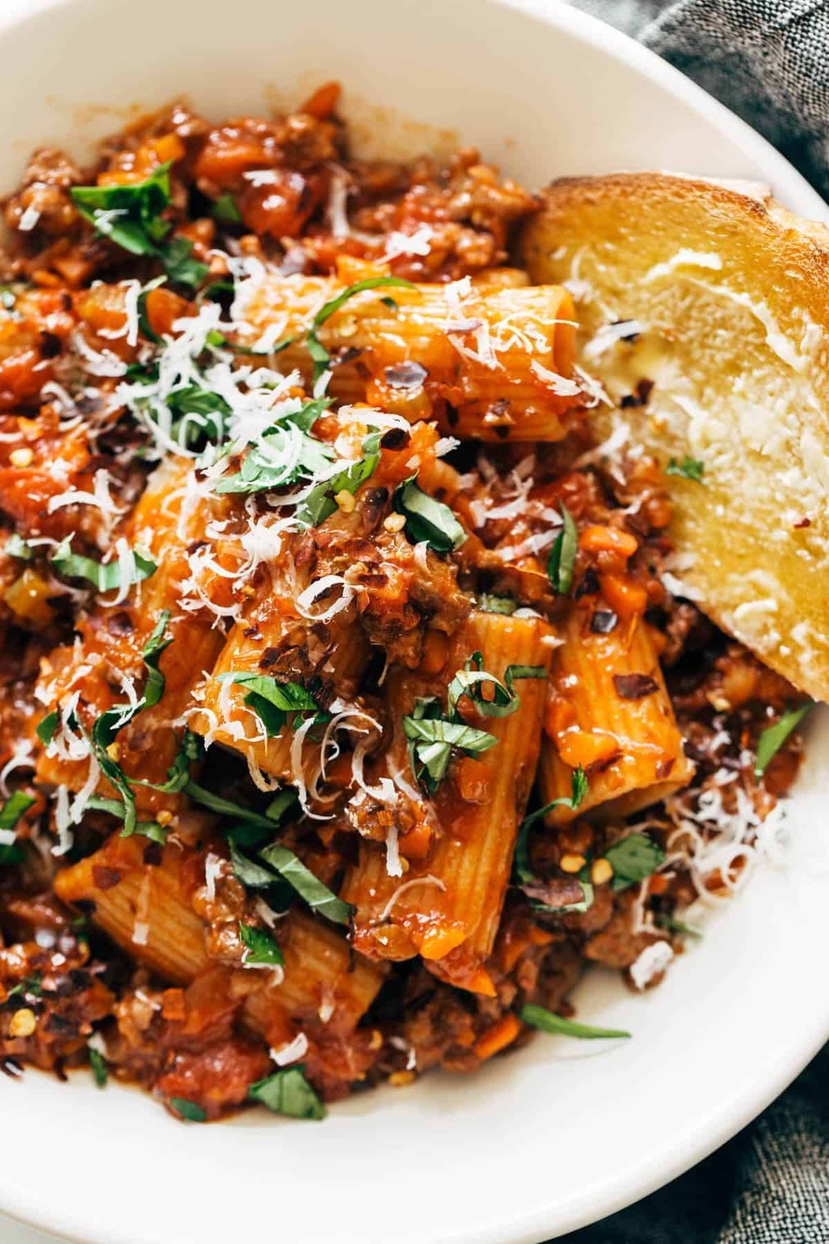 Spicy Sausage Rigatoni in a bowl with bread.