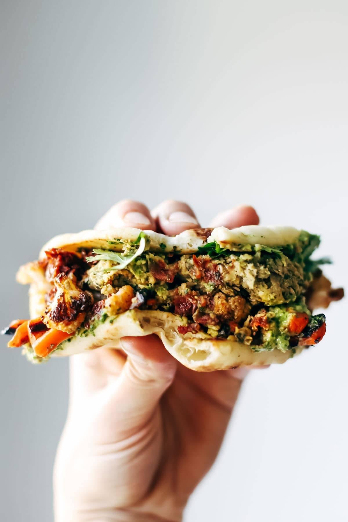 Falafel, roasted veggies, and avocado sauce stuffed between garlic naan.