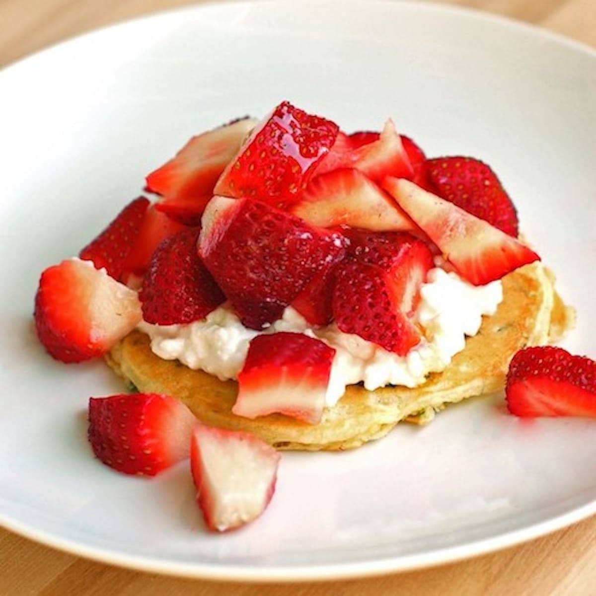Zucchini pancakes with strawberries and whipped cream.