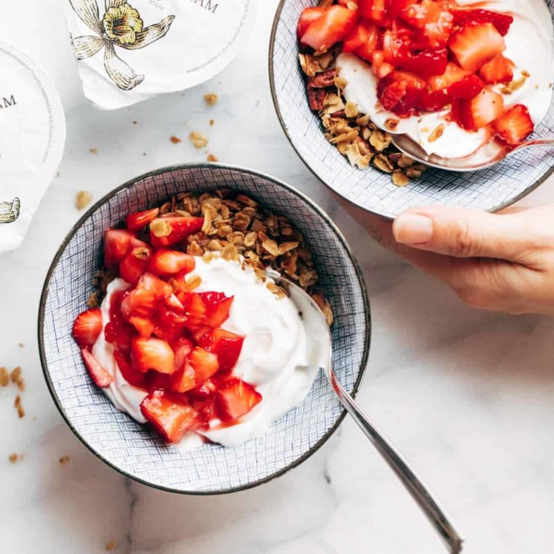 A bowl of granola with yogurt and strawberries on top.