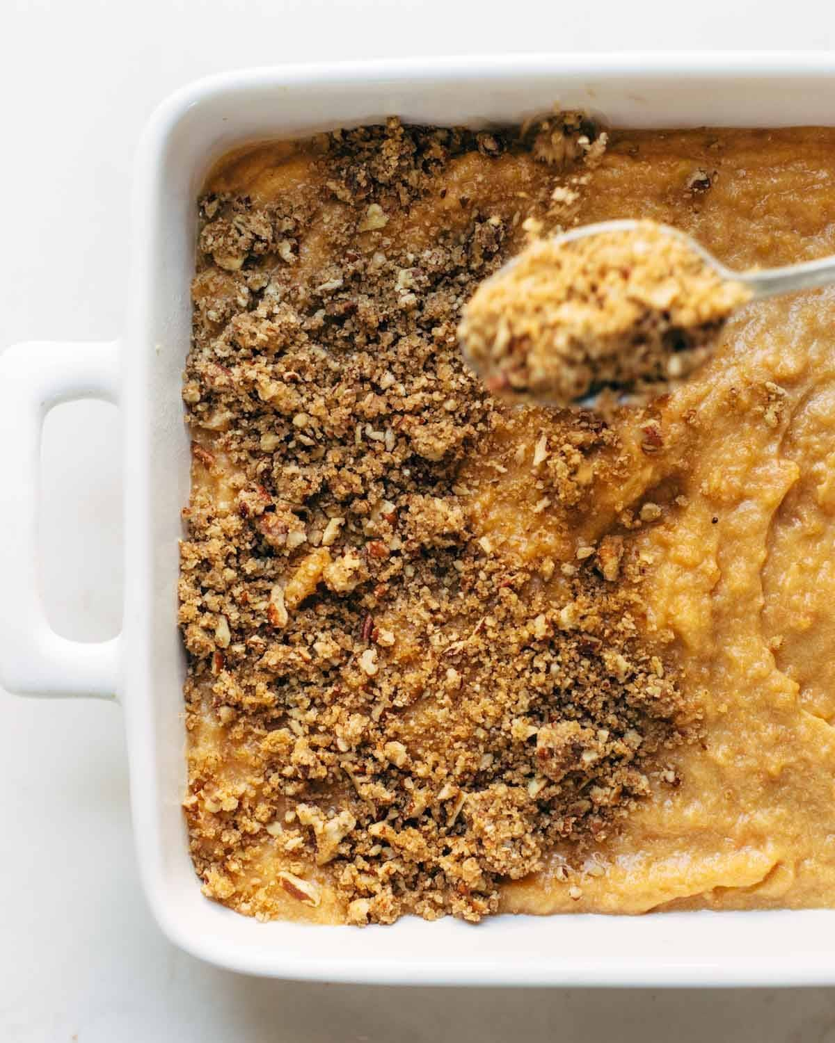 Sweet Potato Casserole with a crunchy brown sugar topping in a dish with a spoon.
