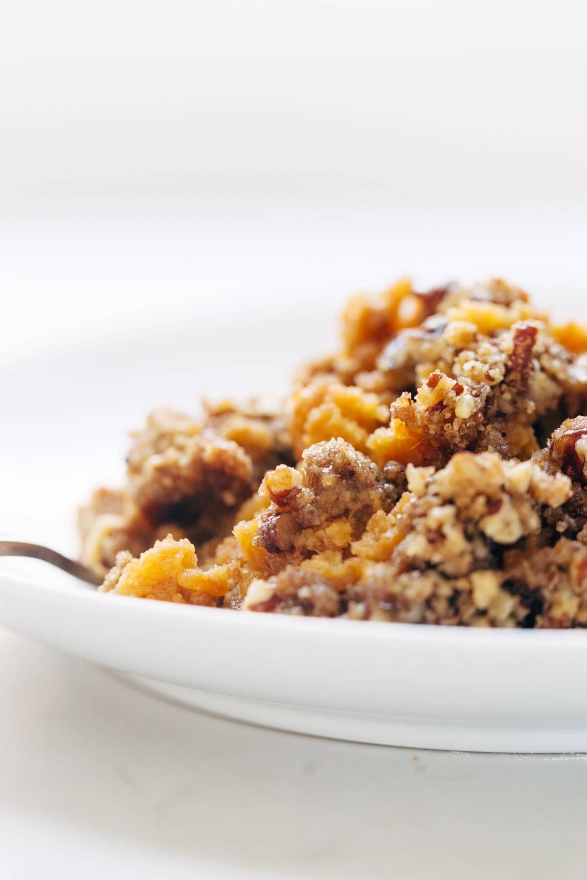 Sweet Potato Casserole with a crunchy brown sugar topping in a bowl with a fork