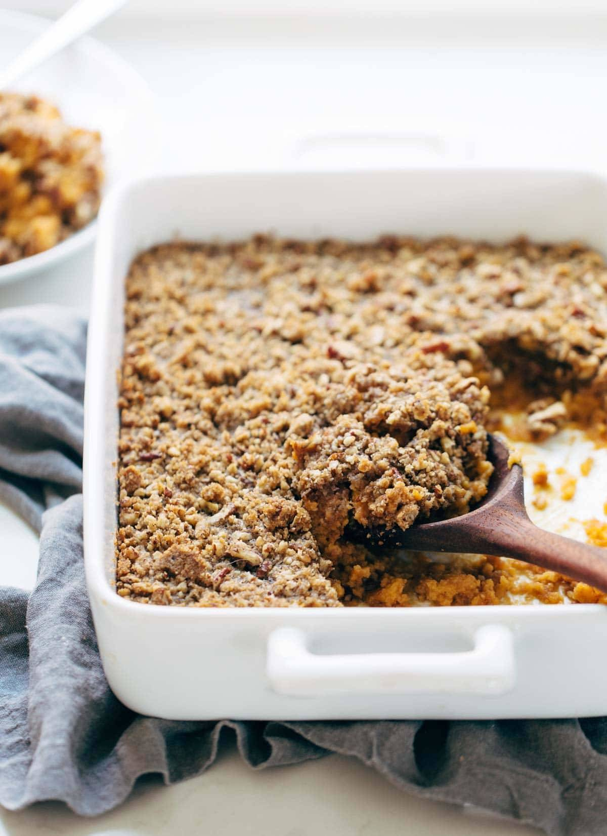 Sweet Potato Casserole with a crunchy brown sugar topping in a dish with a wooden spoon.
