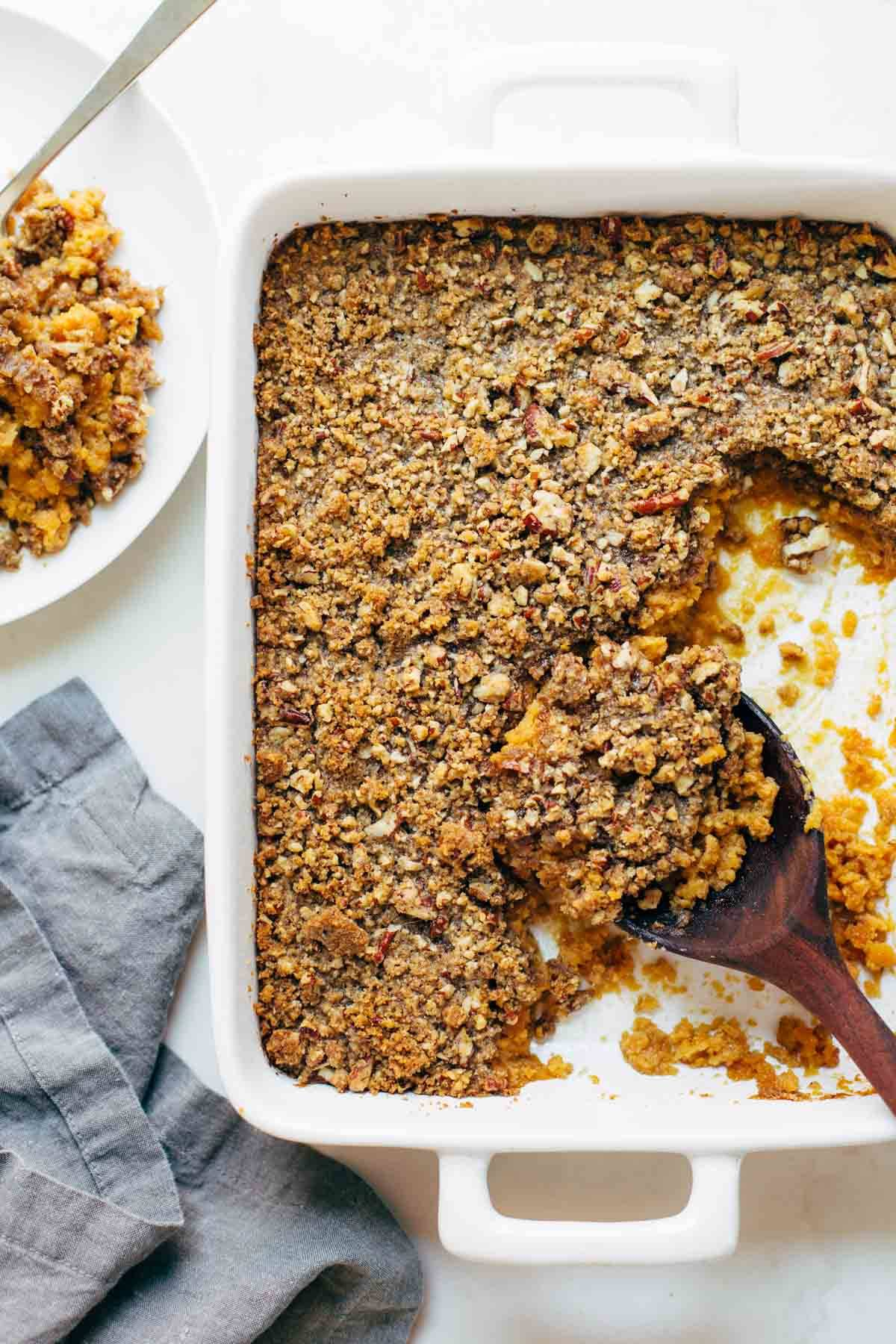Sweet Potato Casserole with a crunchy brown sugar topping with a wooden spoon