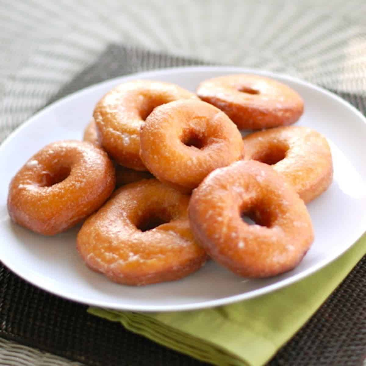 sweet potato doughnuts on a plate on top of a green napkin