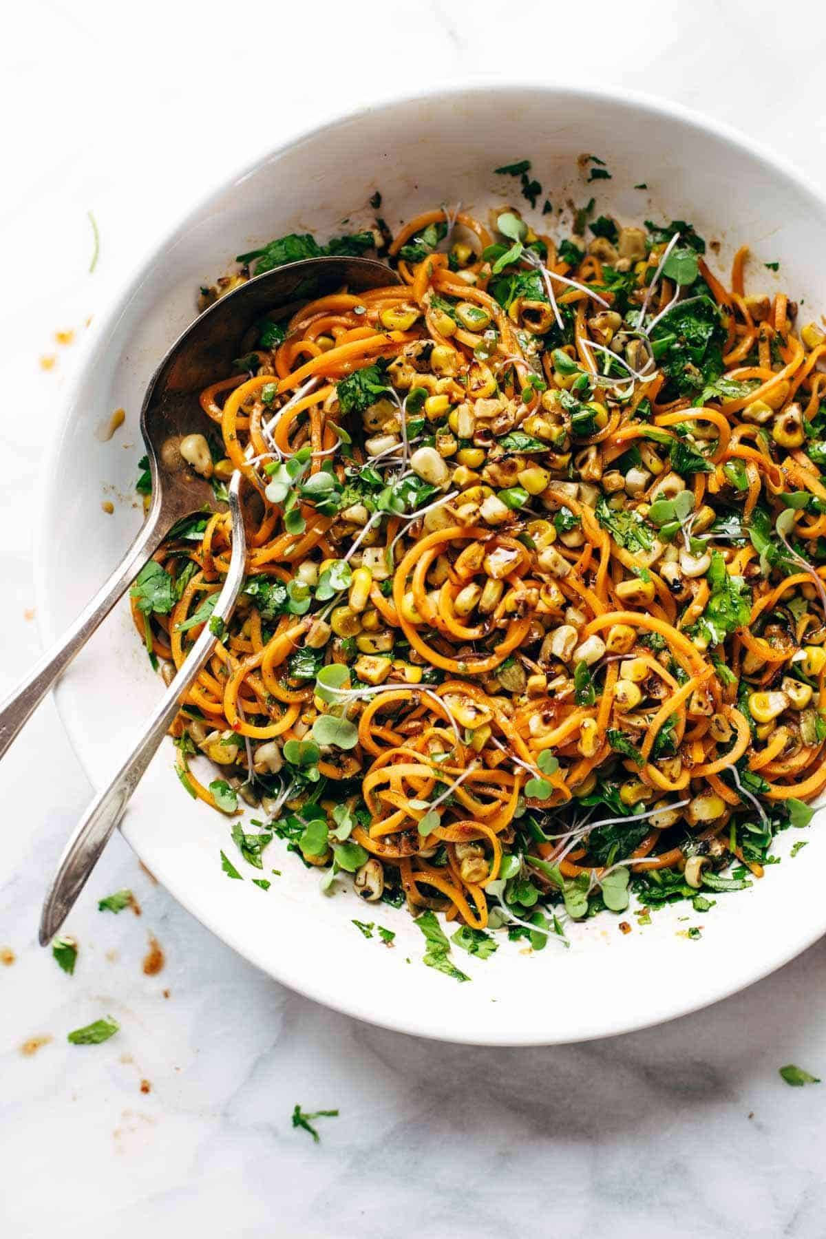 sweet potato noodle salad in a bowl with two spoons
