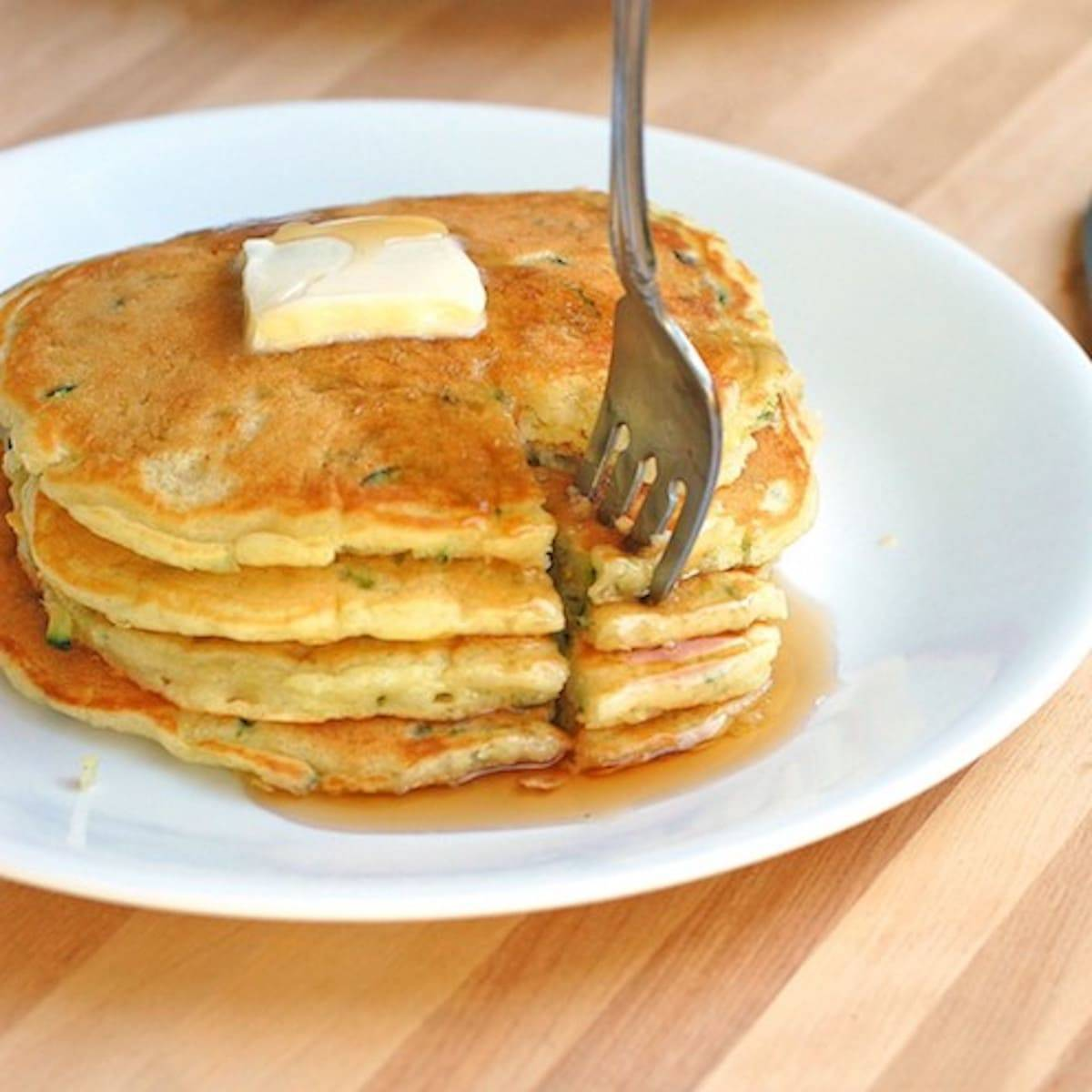 Stack of zucchini pancakes with butter and maple syrup with a fork.