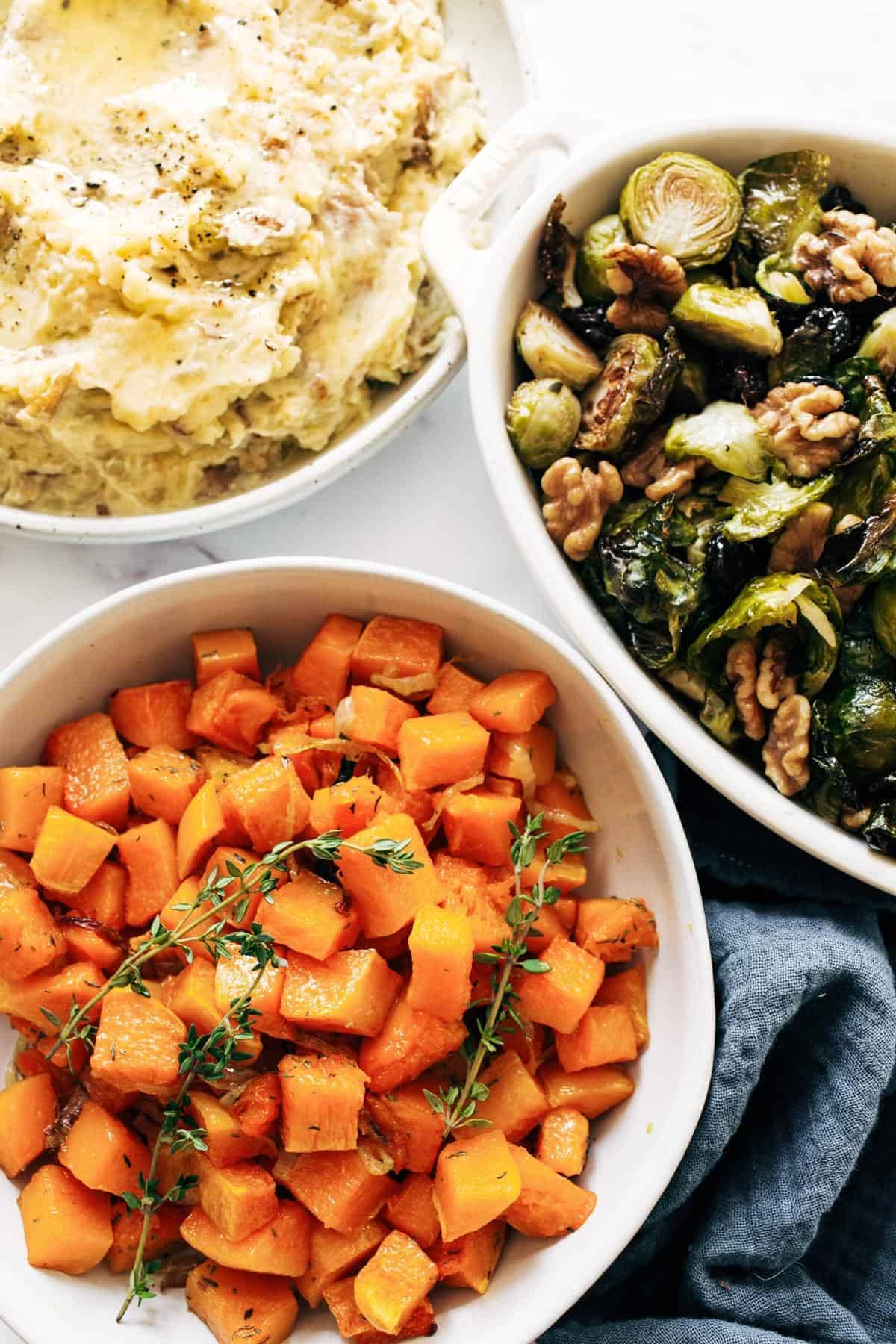 Mashed potatoes, brussels sprouts, and herbed squash in bowls.