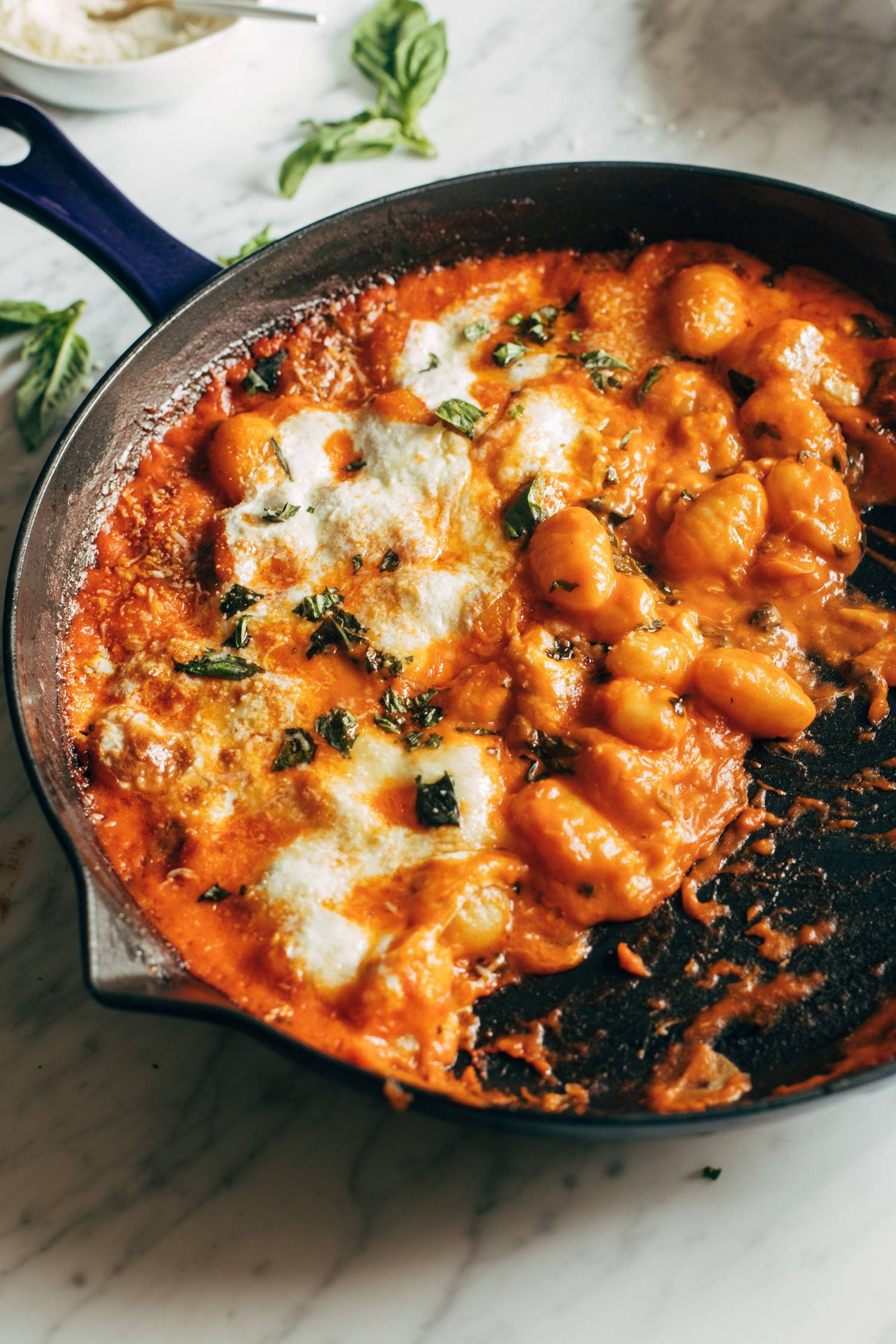 Three cheese baked gnocchi in a cast iron pan.