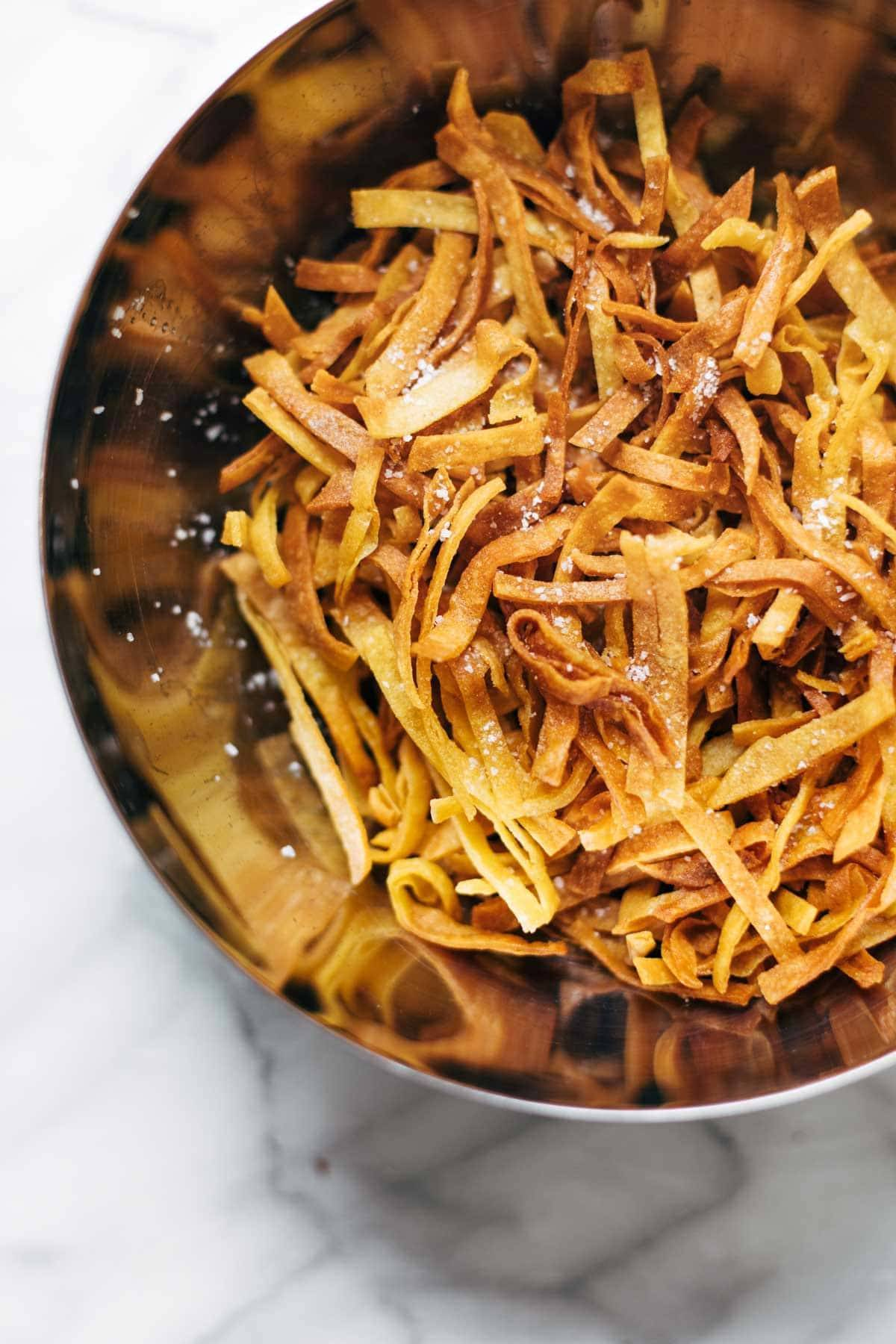 Fried tortilla strips in bowl.