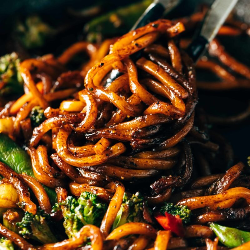 Udon Noodles mixed with fried vegetables and some black pepper in a cooking pan.