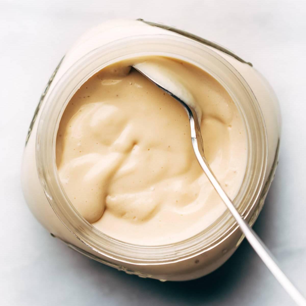 Vegan yogurt in a jar with spoon.