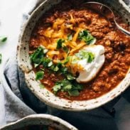 Bowls of chili with shredded cheddar, cilantro, and sour cream.