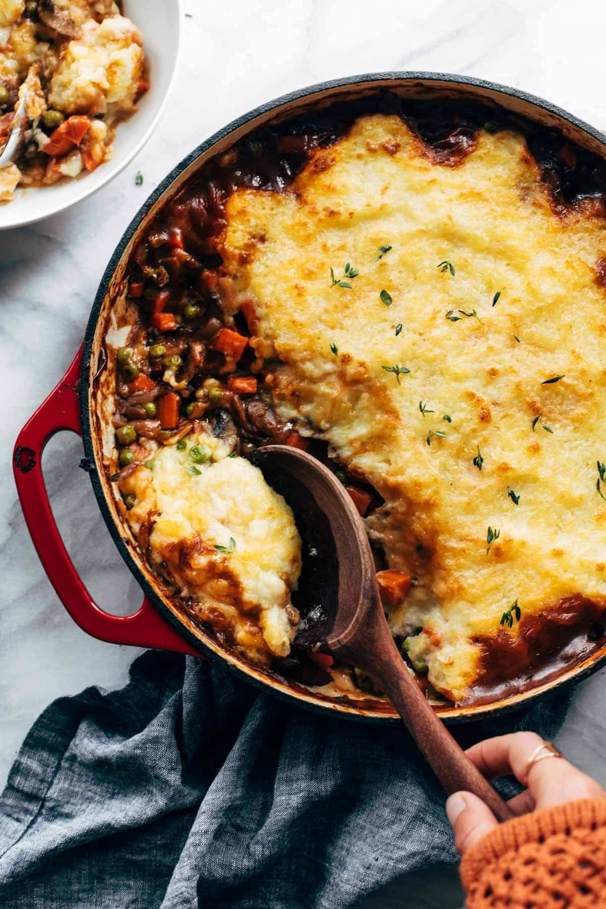 Vegetarian Shepherd's Pie in a red casserole dish being scooped with a wooden spoon