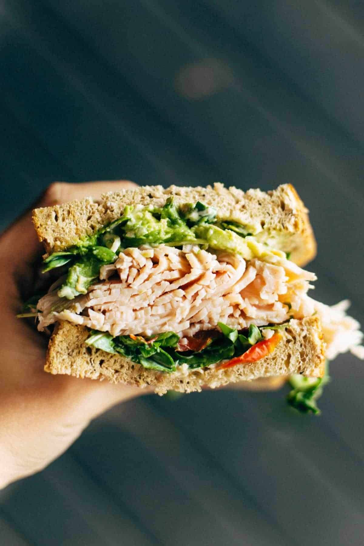 Hand holding a sandwich with lettuce and meat.