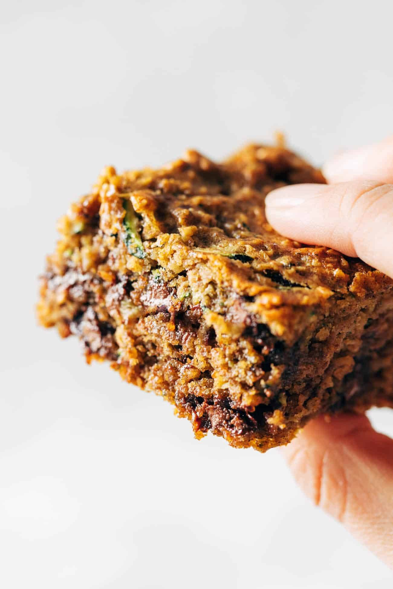 Close-up image of a white hand holding an almond butter chocolate chip zucchini bar.