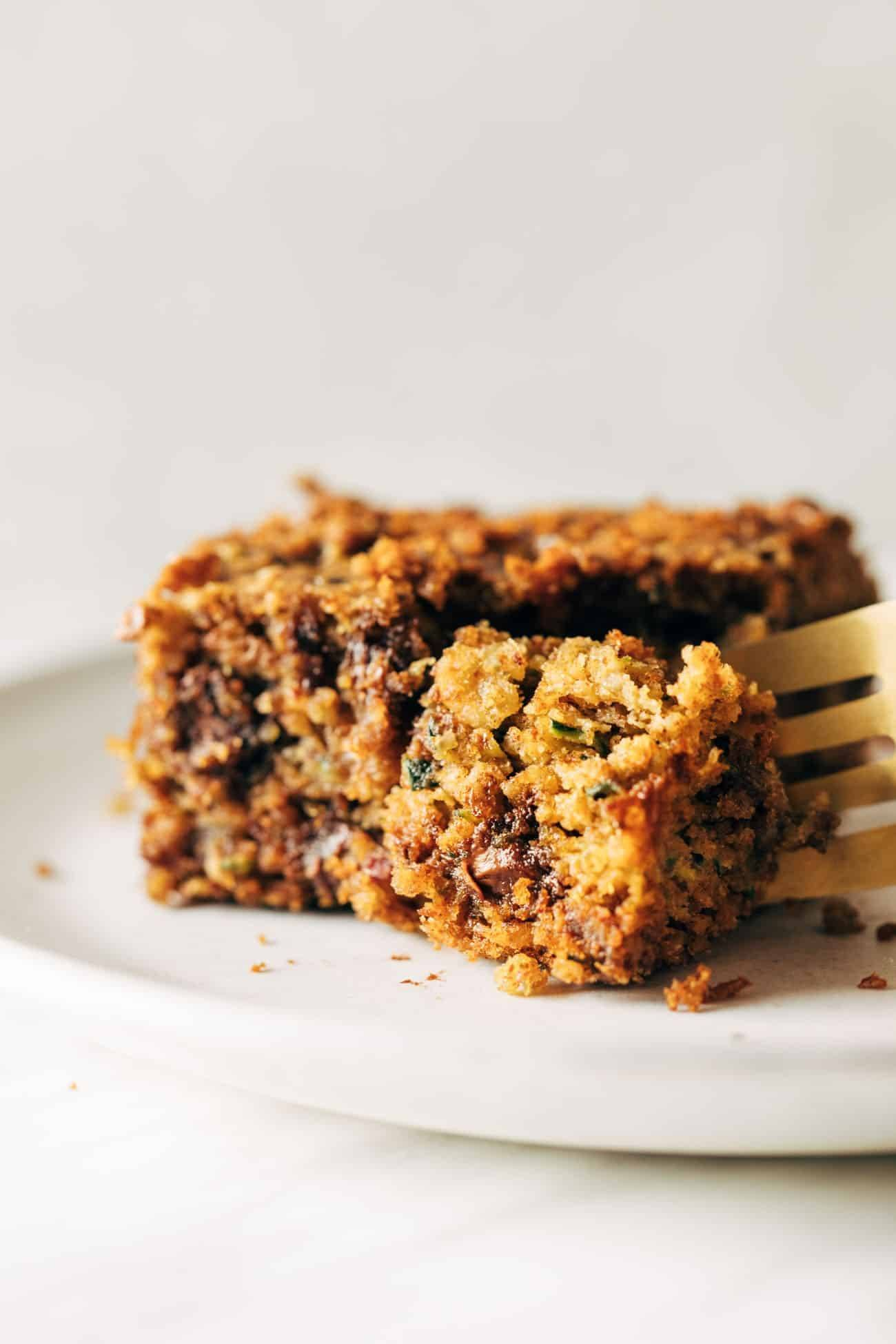 Almond butter chocolate chip zucchini bar on a white plate being cut into with a fork.