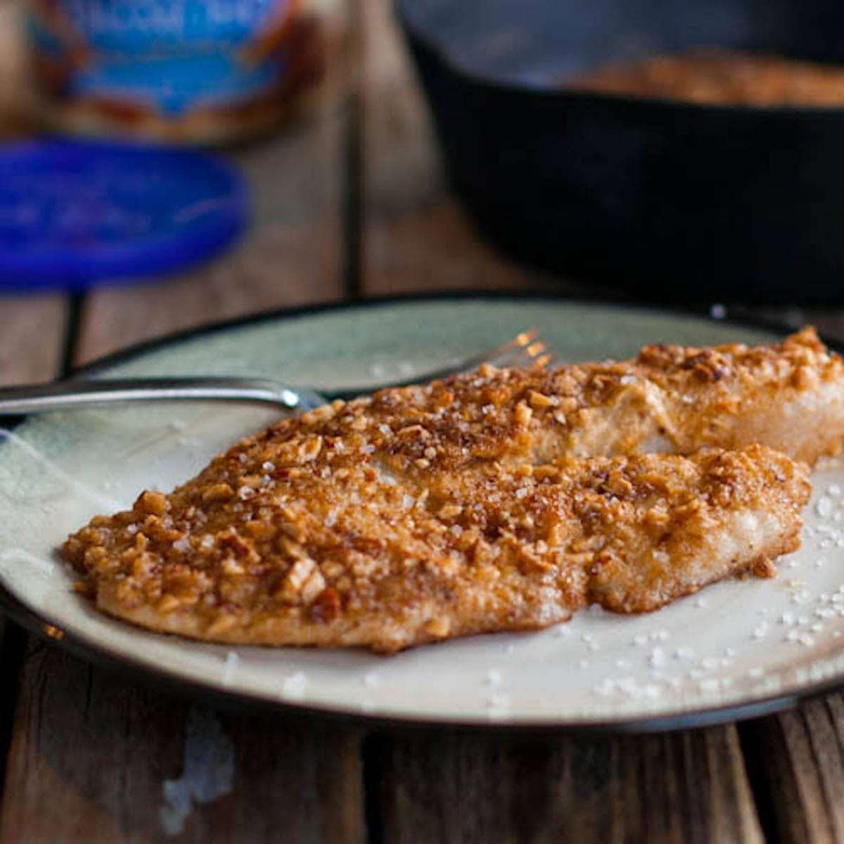 Almond crusted tilapia on a plate with a fork.