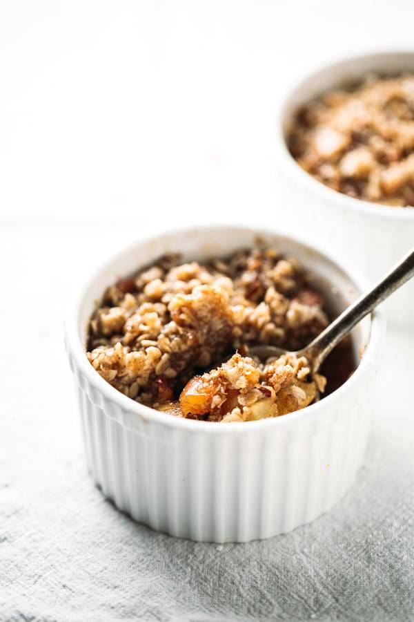 Apple Crisp in a white dish with a spoon.