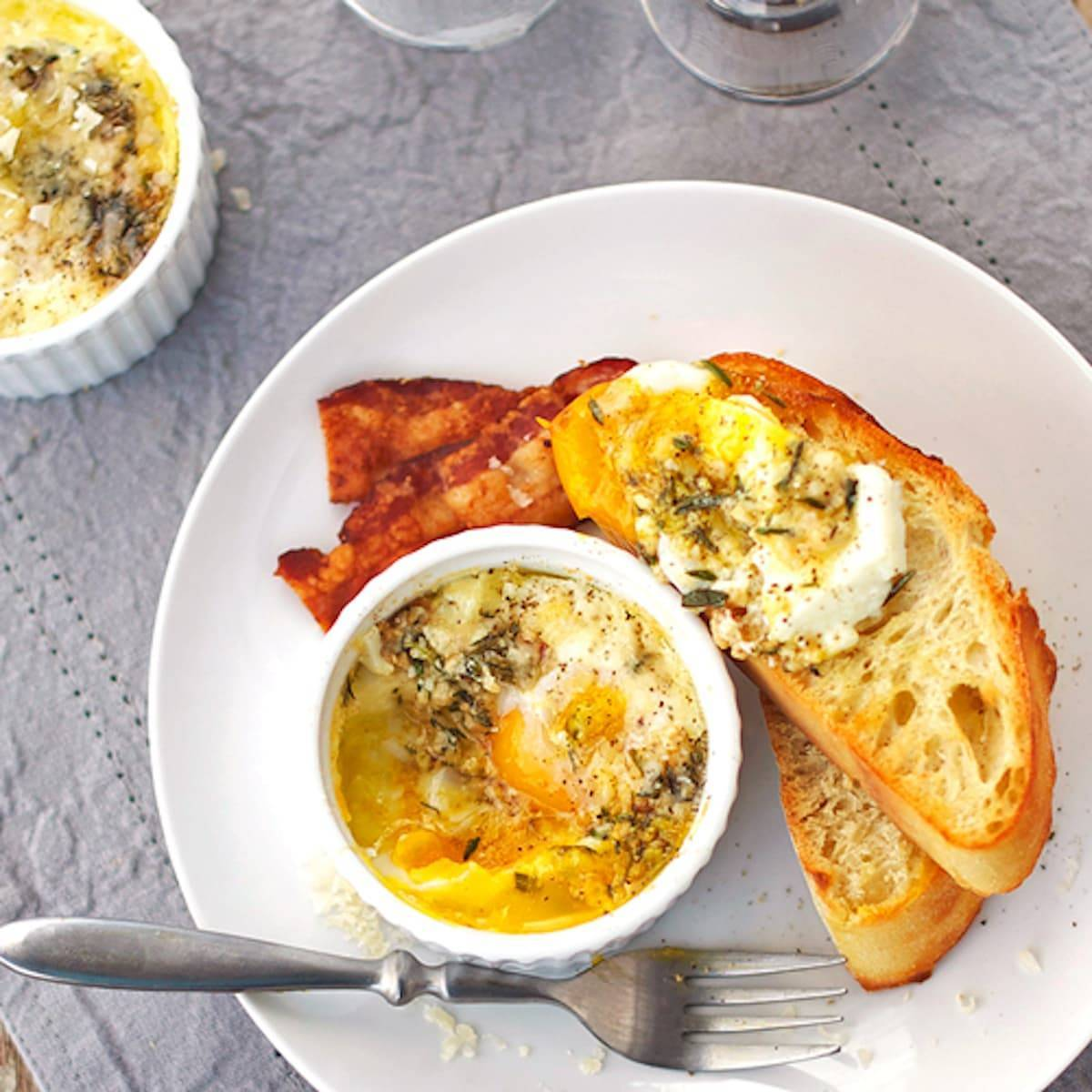 Parmesan baked eggs in a dish and on pieces of bread on a plate.