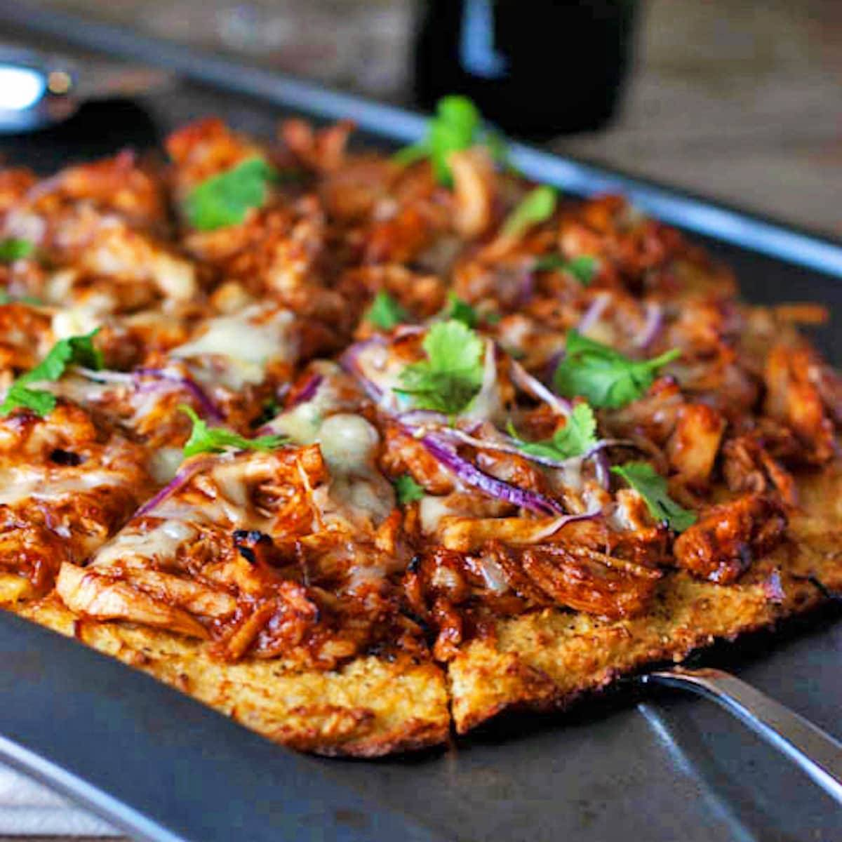 BBQ chicken pizza cut into slices.