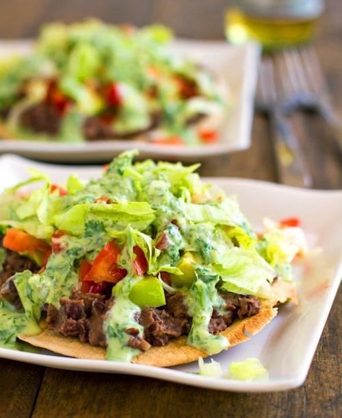 Black bean tostadas drizzled with a homemade healthy cilantro sauce.