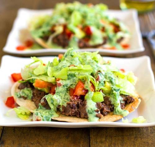 Black bean tostadas drizzled with a homemade healthy cilantro sauce.