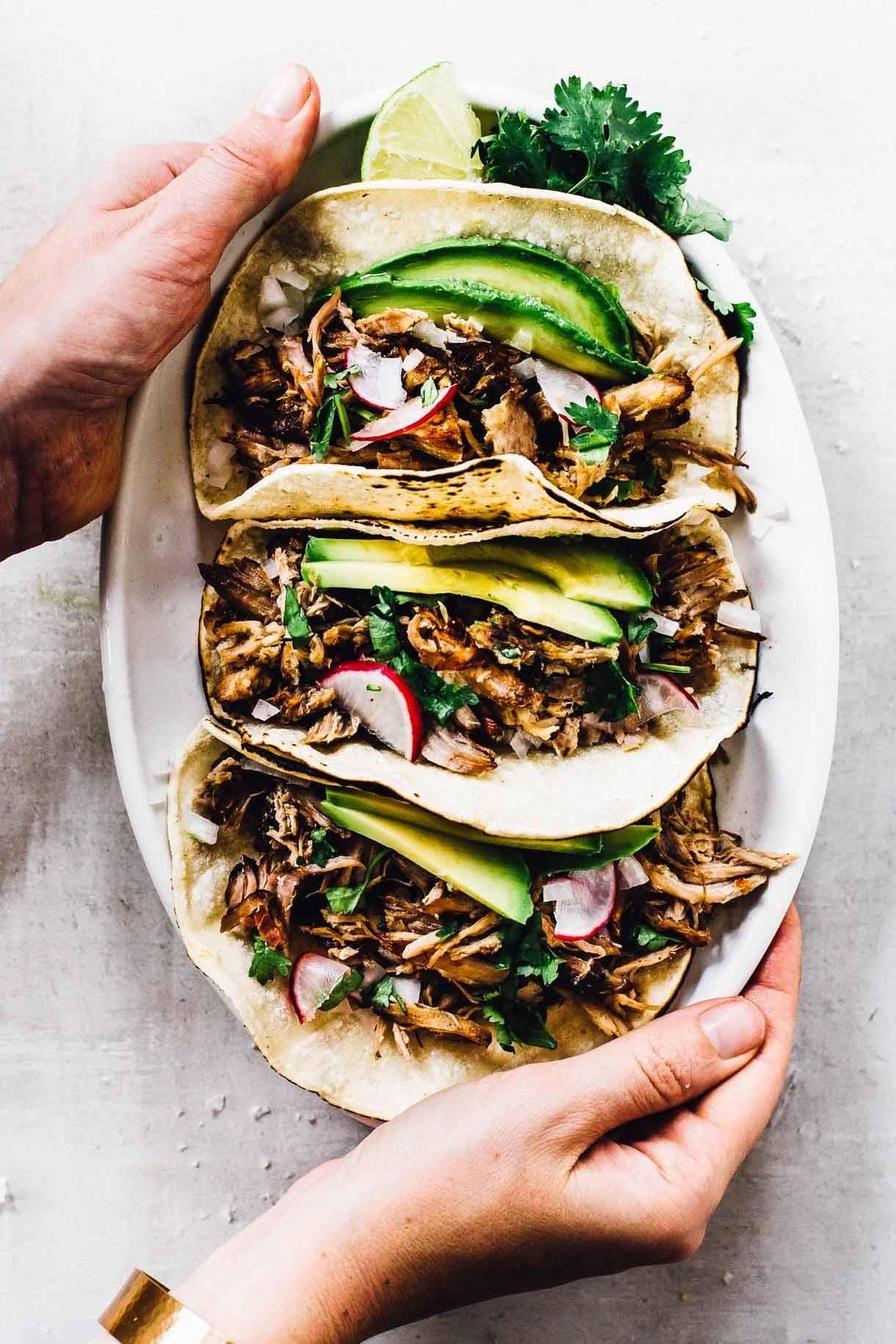 Crockpot carnitas in tacos with avocado.