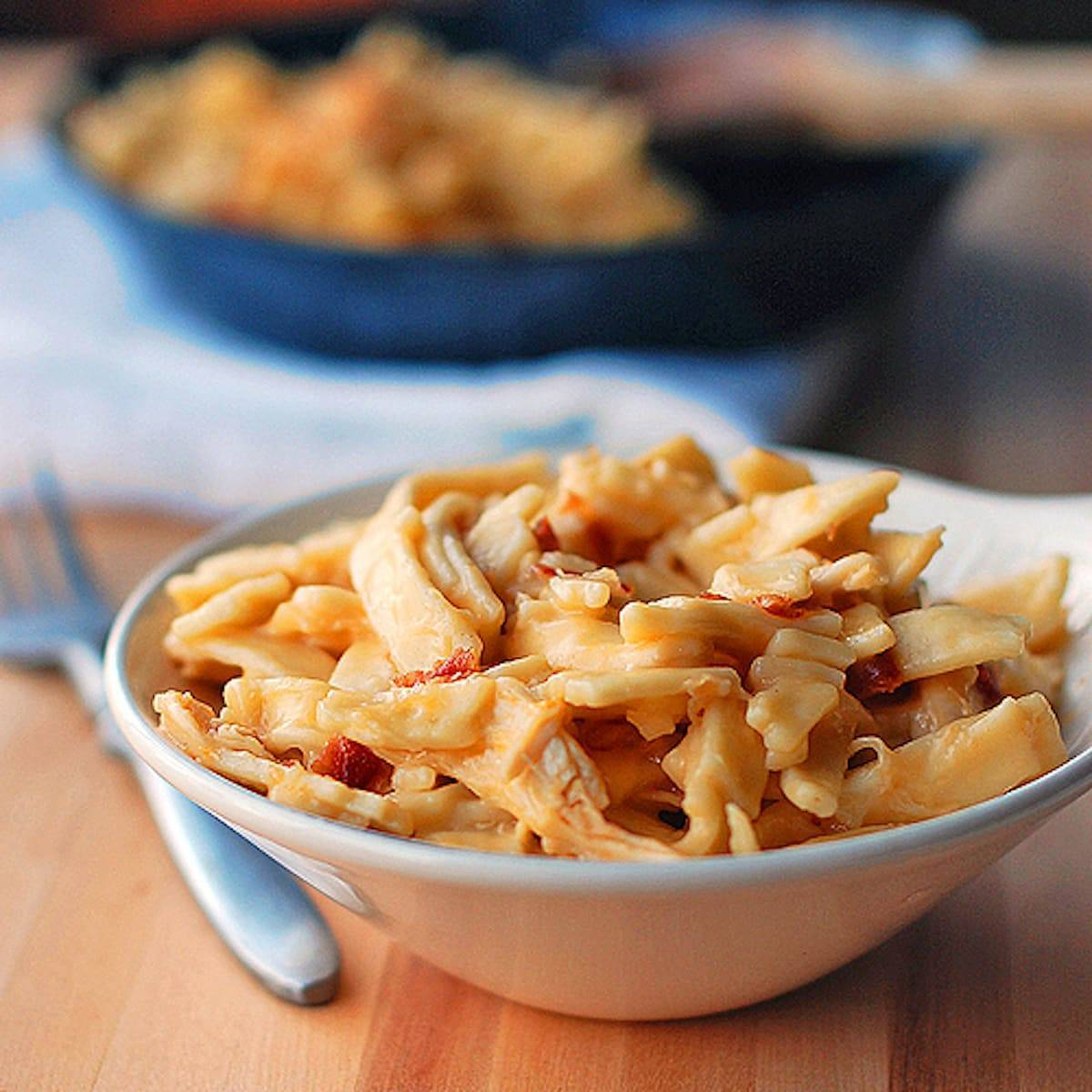 Cheesy chicken noodles coated in a creamy sauce and tossed with shredded chicken in a bowl.