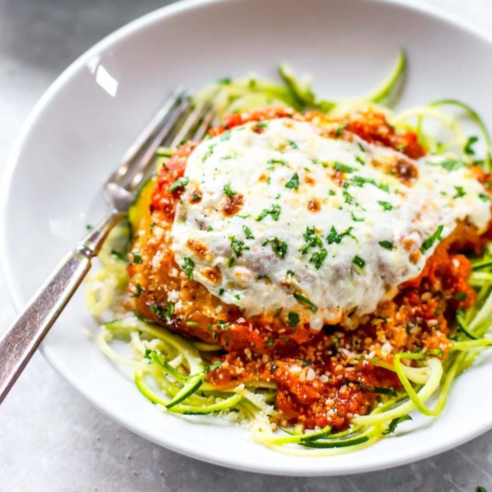 Healthy Chicken Parmesan on a plate with zoodles.