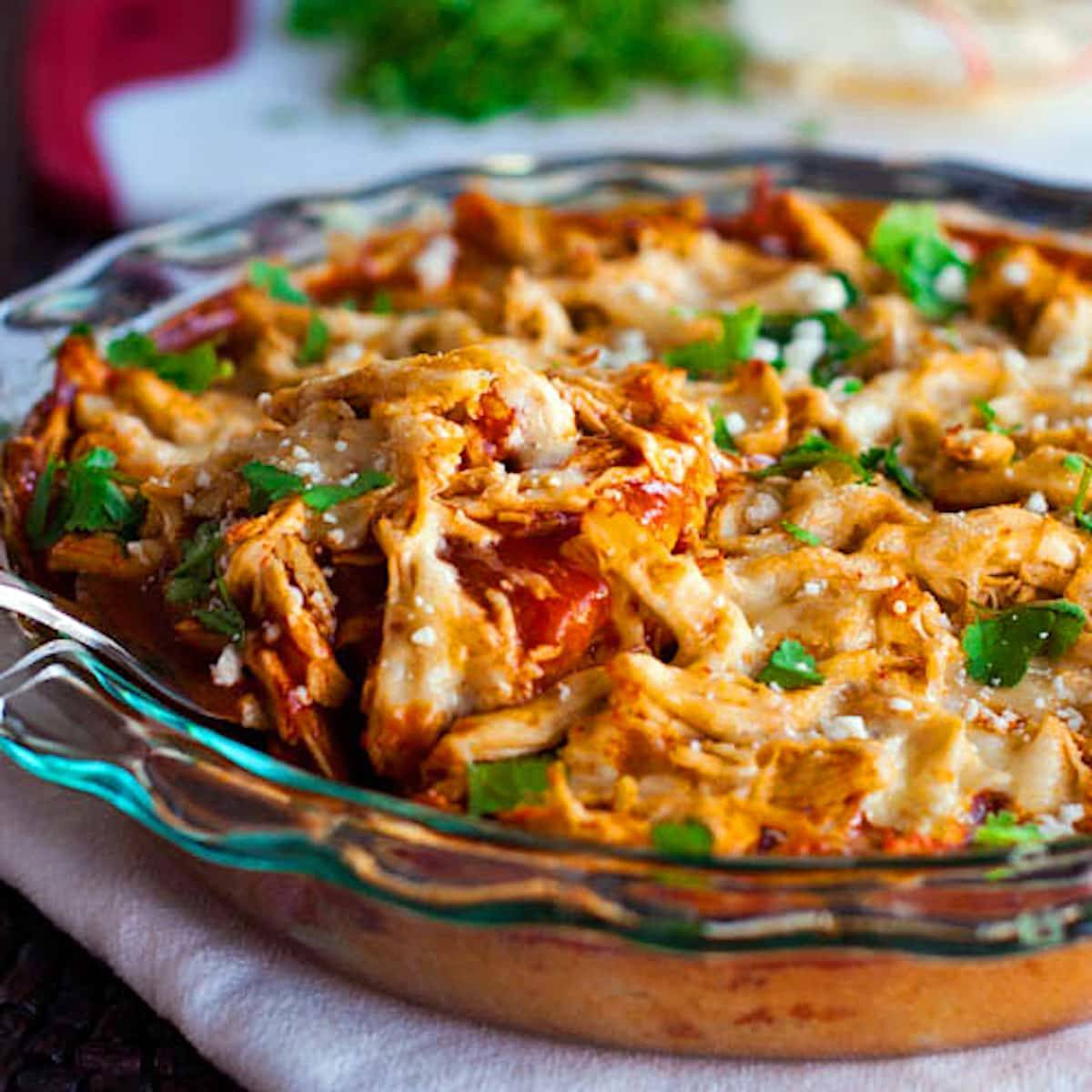 Chicken tamale pie topped with shredded chicken, enchilada sauce, and cheese in a clear dish.