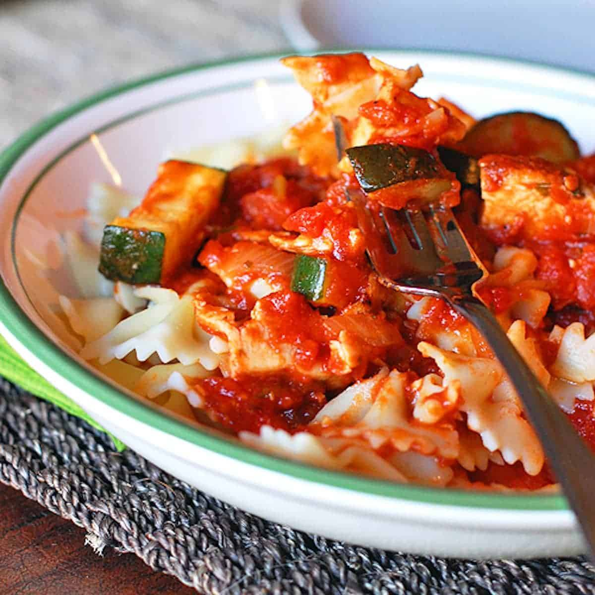 A quick and easy 5 ingredient recipe for chicken zucchini pasta. Made with bowties, tomato sauce, sauteed zucchini, shredded chicken, and Parmesan. | pinchofyum.com