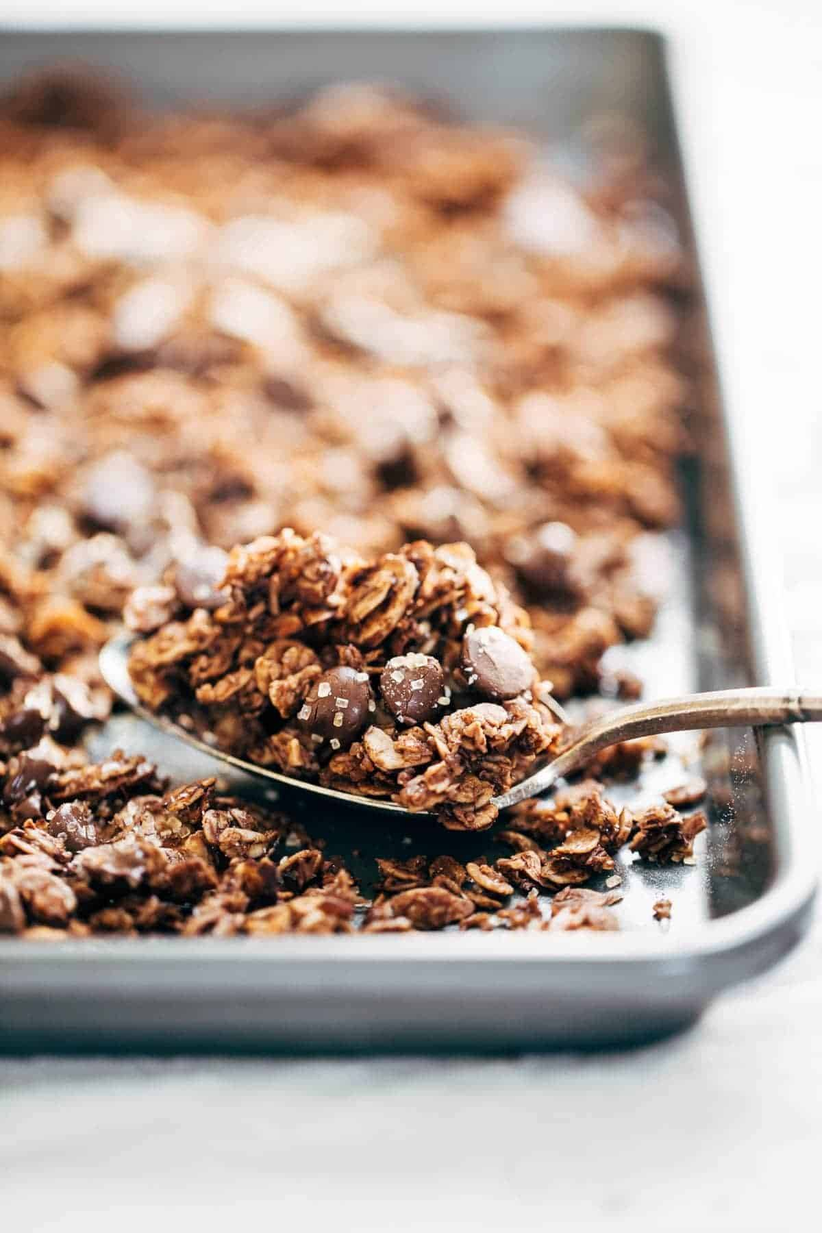 Chocolate Granola with almonds, oats, coconut flakes, chocolate chips, topped with crunchy sugar and sea salt on a pan and on a spoon.