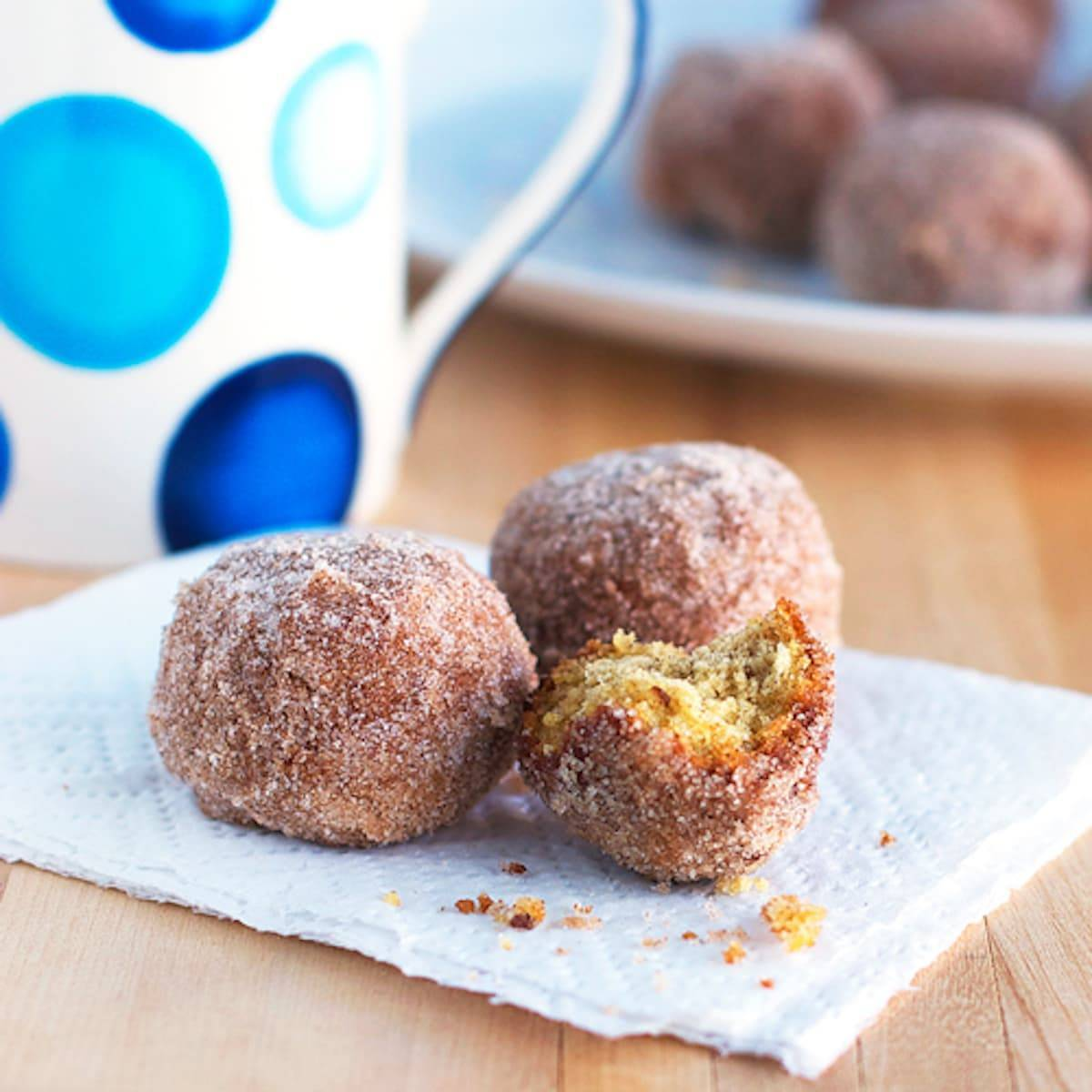 Cinnamon sugar donut balls with crumbs on a napkin.