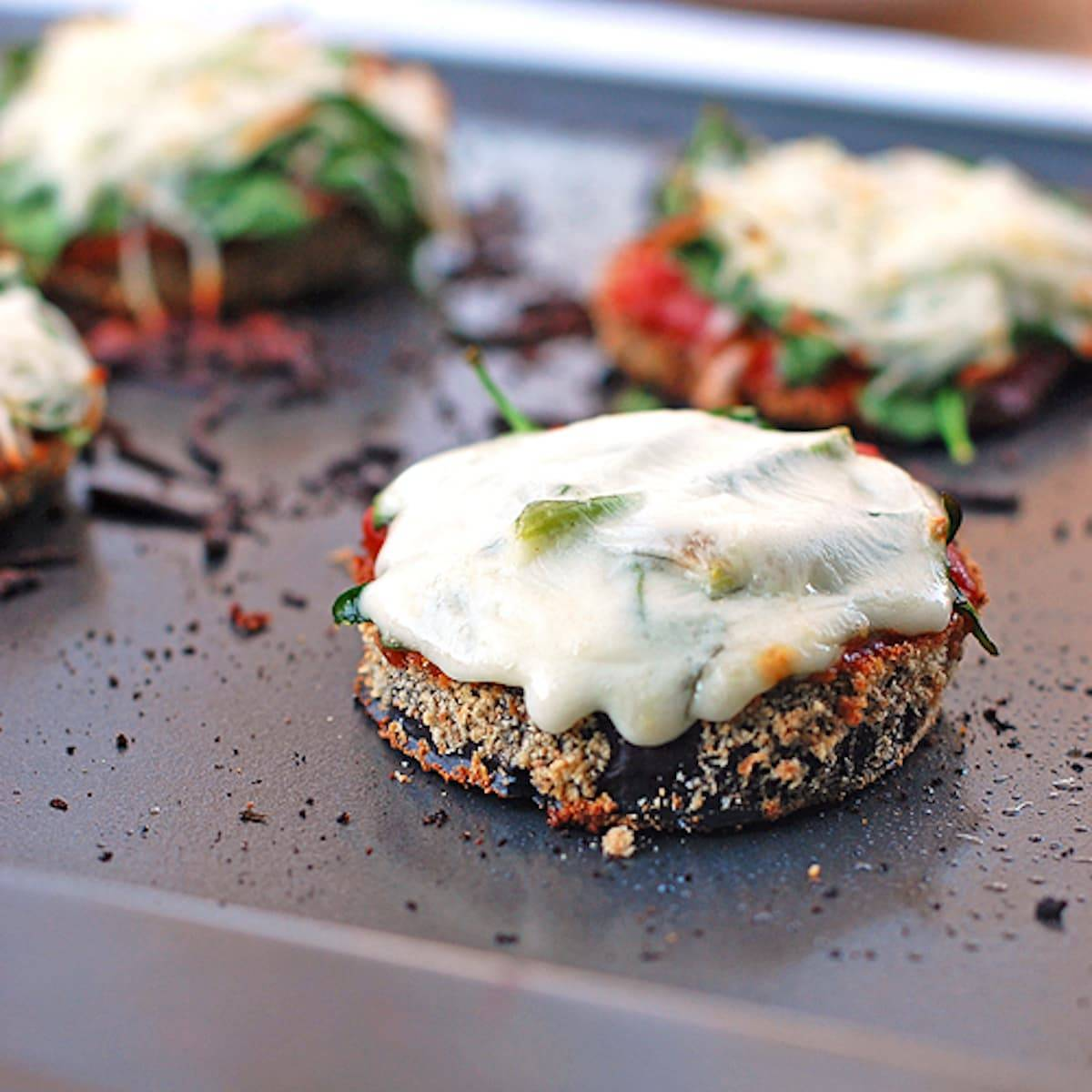 These little eggplant pizzas are baked slices of breaded eggplant topped with marinara and melted cheese. Simple, healthy, delicious! | pinchofyum.com