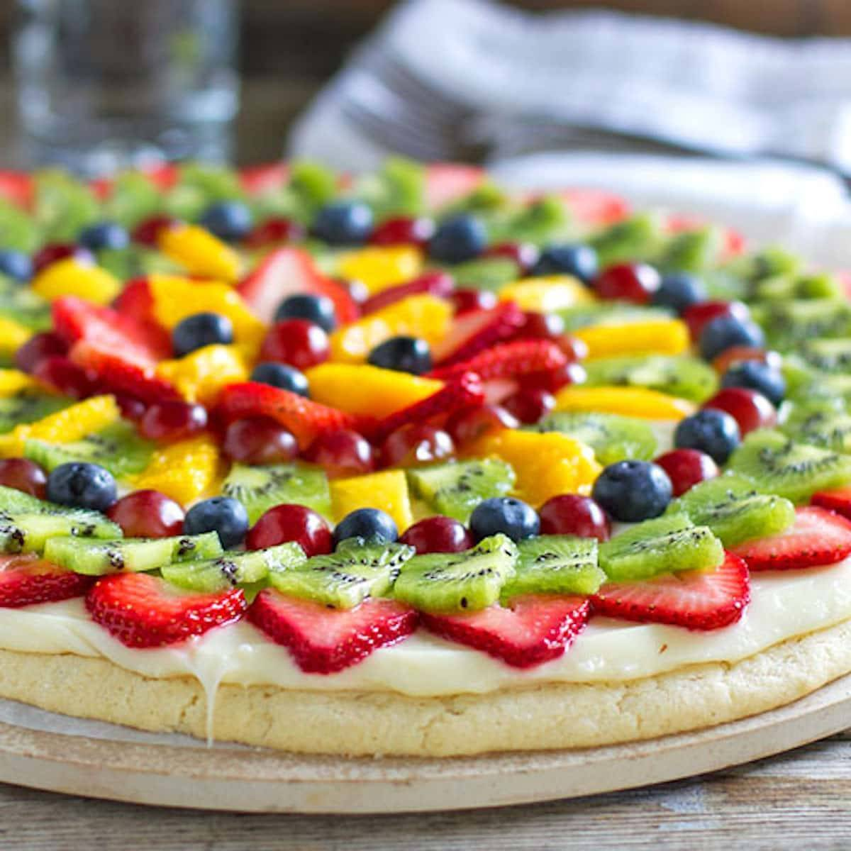 Fruit pizza with a soft sugar cookie crust with a cream cheese frosting and topped with sliced fruit.