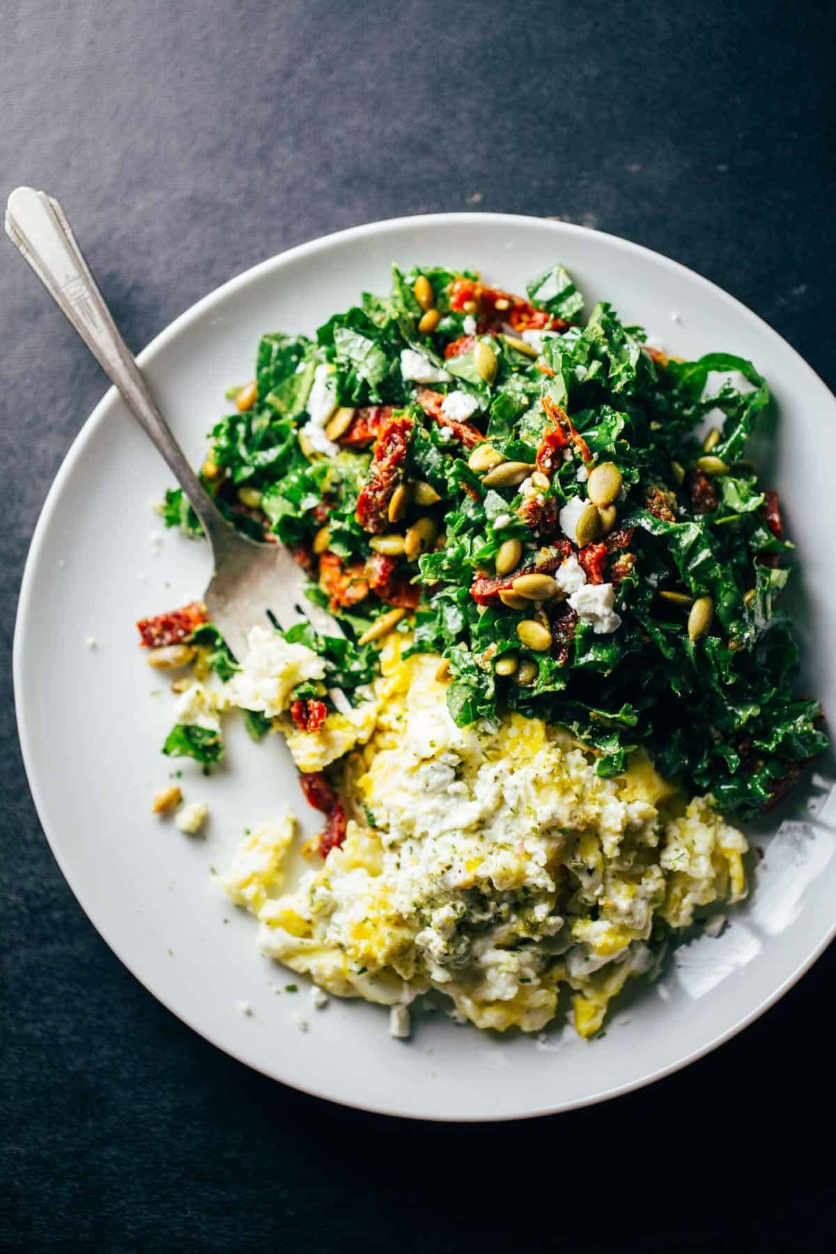 Goat Cheese Scrambled Eggs with Pesto Veggies on a white plate with a fork.