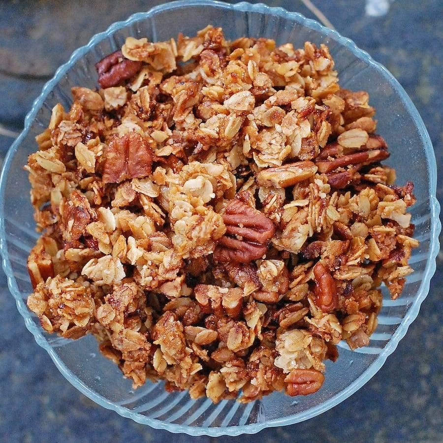 Pecan granola in a glass bowl.